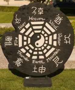 μαύρος πέτρινος τροχός με το σύμβολο γιν-γιανγκ