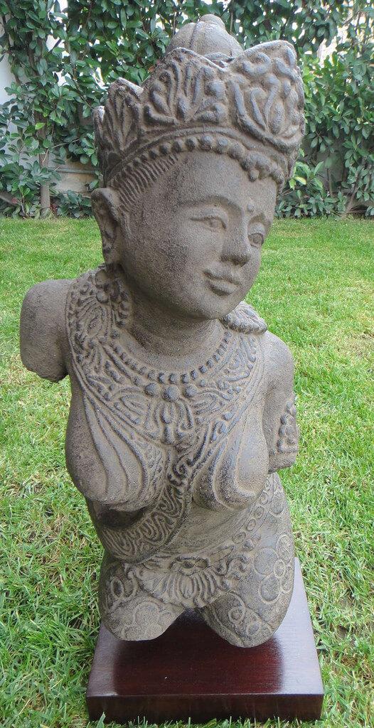 πέτρινο άγαλμα που απεικονίζει μια γυναίκα επάνω σε ξύλινο βάθρο