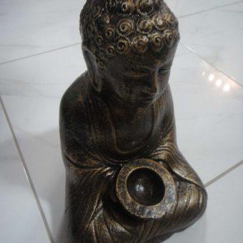 άγαλμα το οποίο απεικονίζει τον Βούδα με ένα κερί